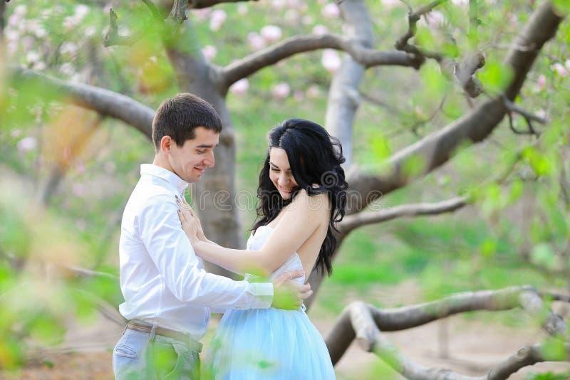 La jeunes femme et brune caucasiennes équipent étreindre près de l'arbre de floraison photographie stock