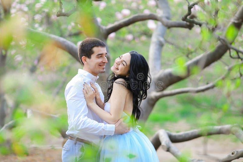 La jeunes femme et brune de sourire équipent étreindre près de l'arbre de floraison image libre de droits