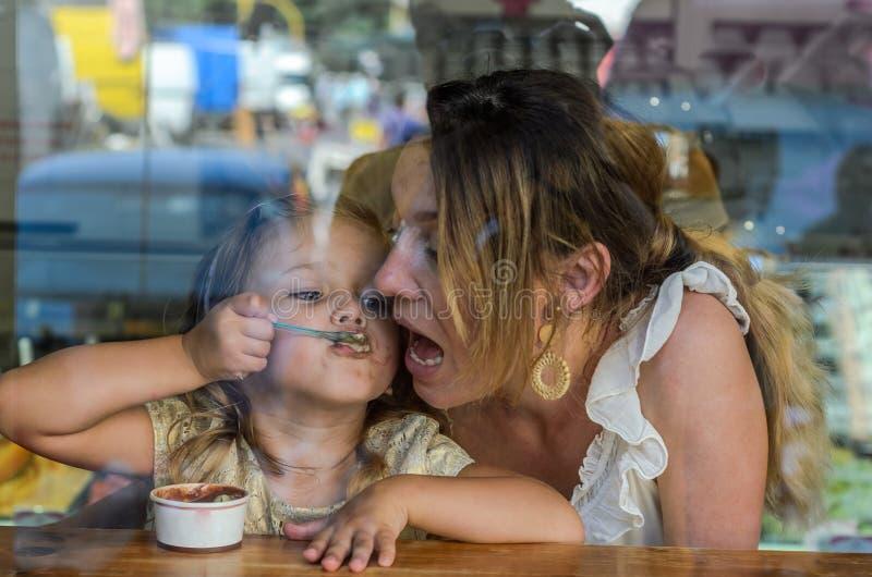 La jeunes mère et fille mangent la crème glacée dans un café, la famille heureuse, vue par la fenêtre image stock