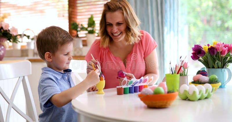 La jeunes mère et fils heureux peignent des oeufs de pâques photo libre de droits