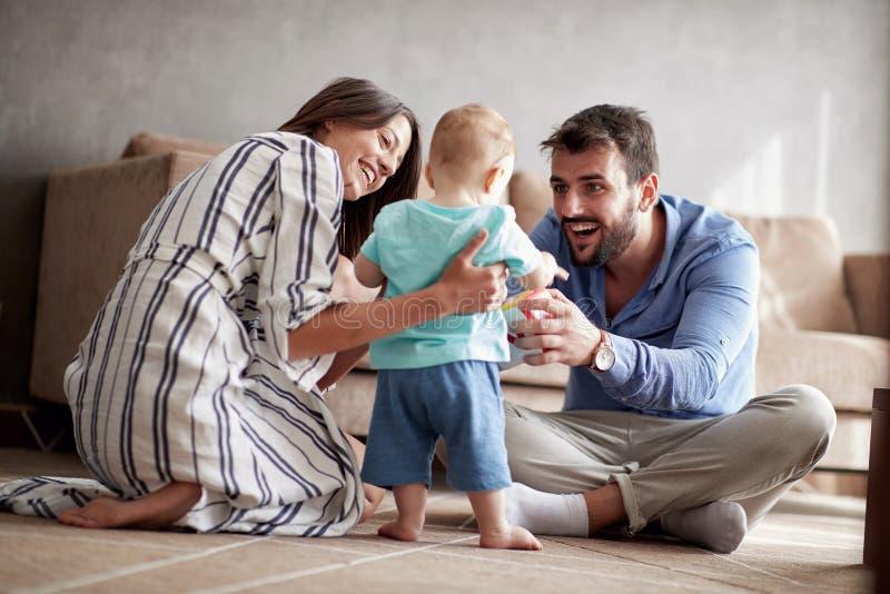 La jeunes mère et père a l'amusement jouant avec un bébé au hom images stock