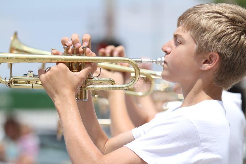 La jeunesse joue la trompette dans le défilé en petite ville Amérique image libre de droits
