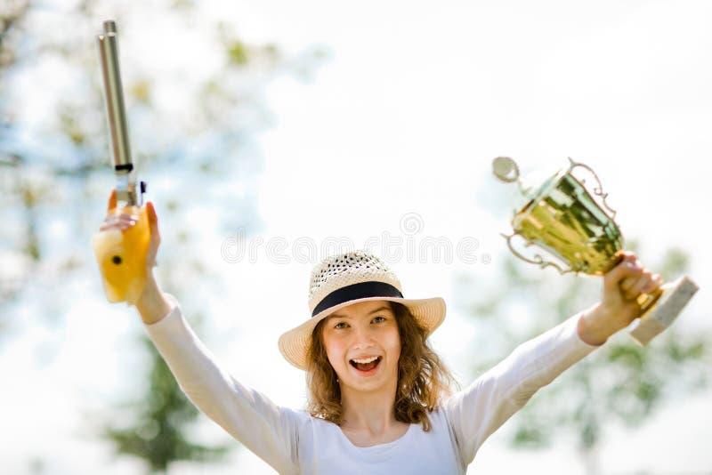 La joie du gagnant, tireuse de jeune fille de pistolet d'air 10 m?tres appr?cient photos stock