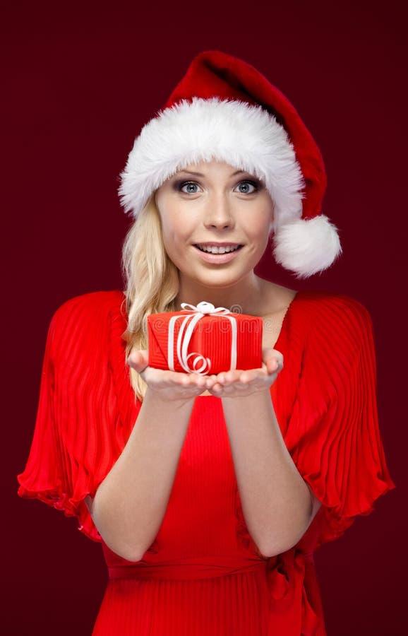 La jolie dame dans le capuchon de Noël remet un présent image stock
