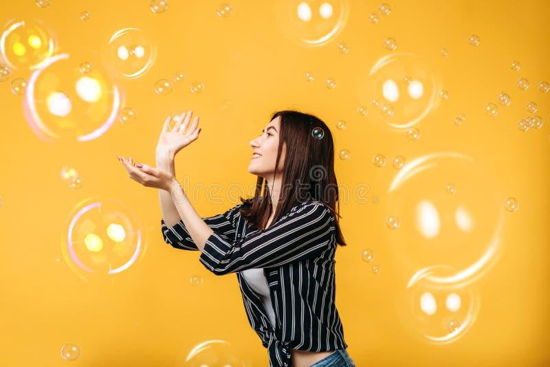 La jolie femme attrape la bulle de savon photographie stock
