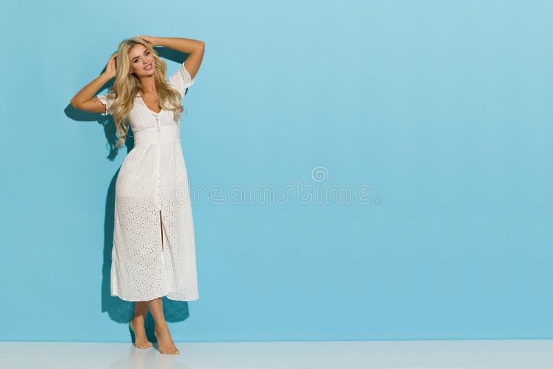 La jolie femme blonde dans la robe blanche d'été se tient contre le mur bleu photo stock