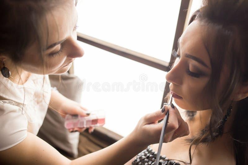 La jolie femme composent l'artiste s'appliquant le maquillage à la belle fille de Latina photos stock
