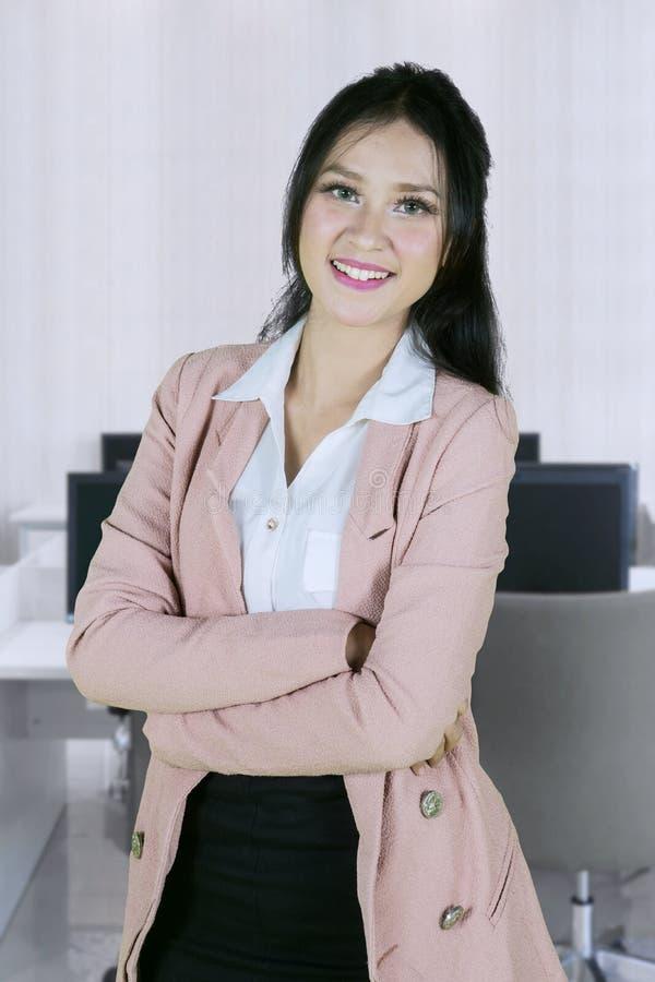 La jolie femme d'affaires a plié ses bras dans le bureau image libre de droits