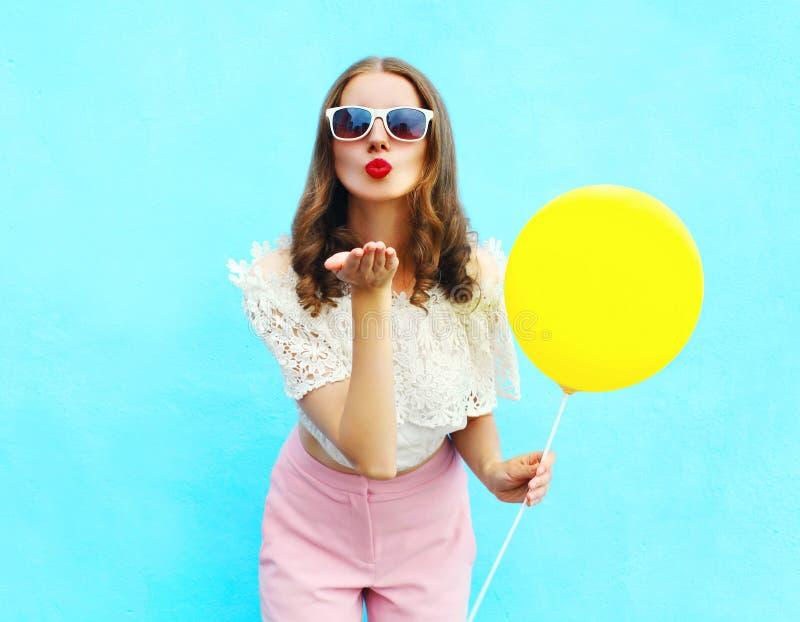 La jolie femme dans des lunettes de soleil avec le ballon à air envoie un baiser d'air au-dessus de bleu coloré photos libres de droits
