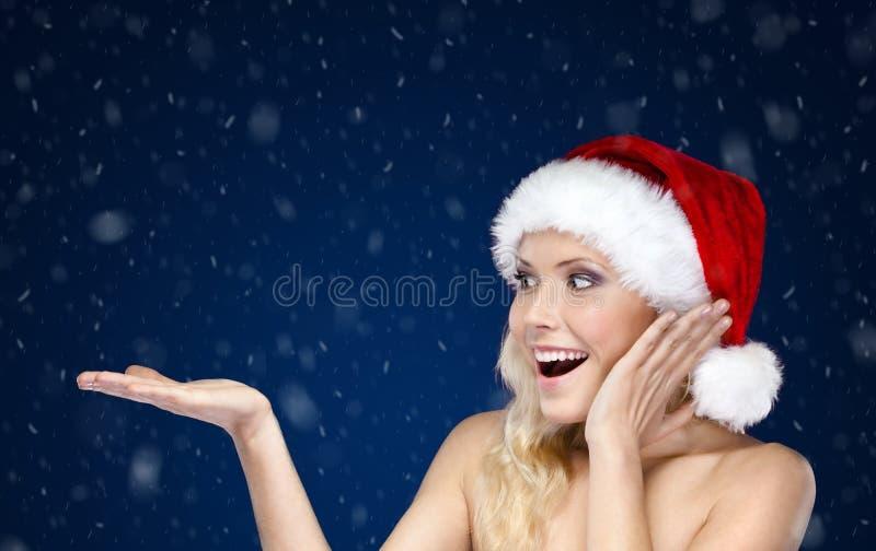 La jolie femme dans le capuchon de Noël fait des gestes la paume vers le haut images stock