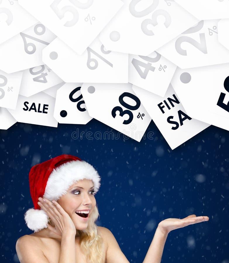 La jolie femme dans le chapeau de Noël fait des gestes la paume vers le haut des prix spéciaux photographie stock libre de droits