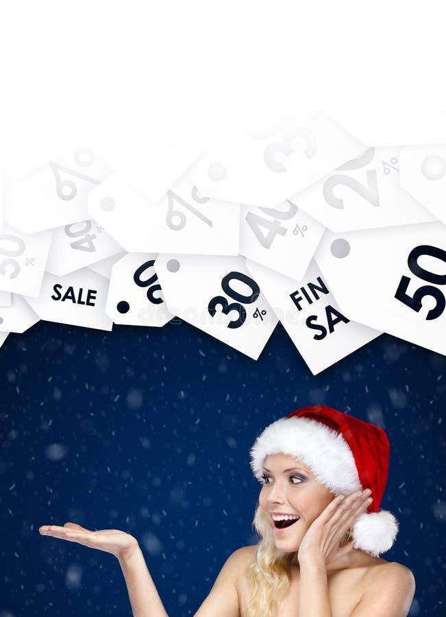 La jolie femme dans le chapeau de Noël montre la remise saisonnière sur des cadeaux image stock