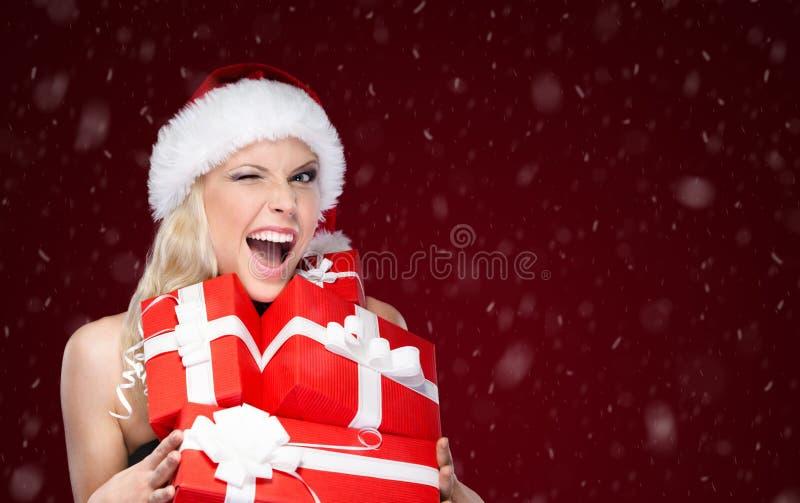 La jolie femme dans le chapeau de Noël tient un ensemble de présents photos libres de droits