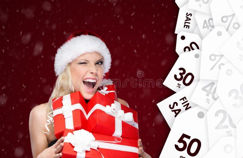 La jolie femme dans le chapeau de Noël tient un ensemble de présents de vente photographie stock
