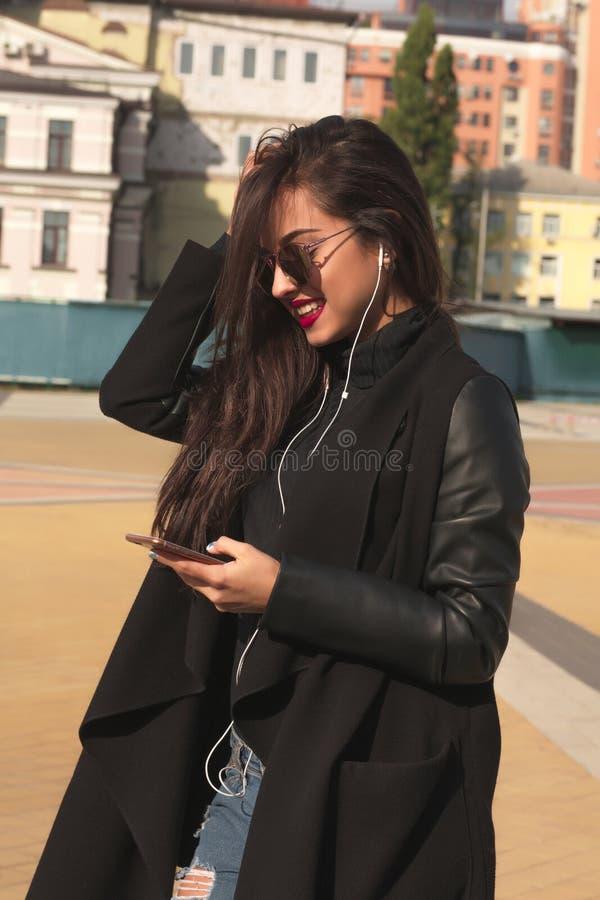 La jolie femme de sourire de brune écoutent musique au téléphone mobile, photos libres de droits