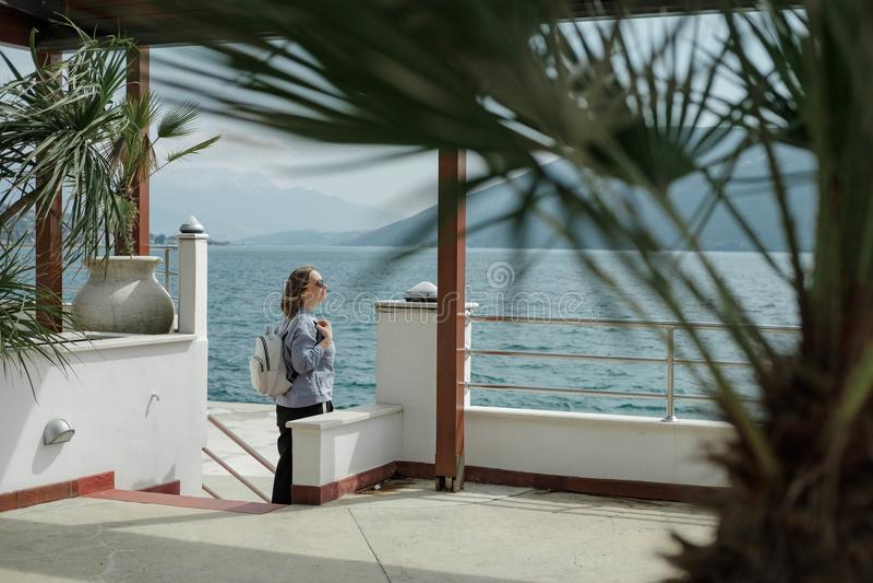 La jolie femme de touristes apprécie la vue de la mer et des montagnes dedans photo libre de droits