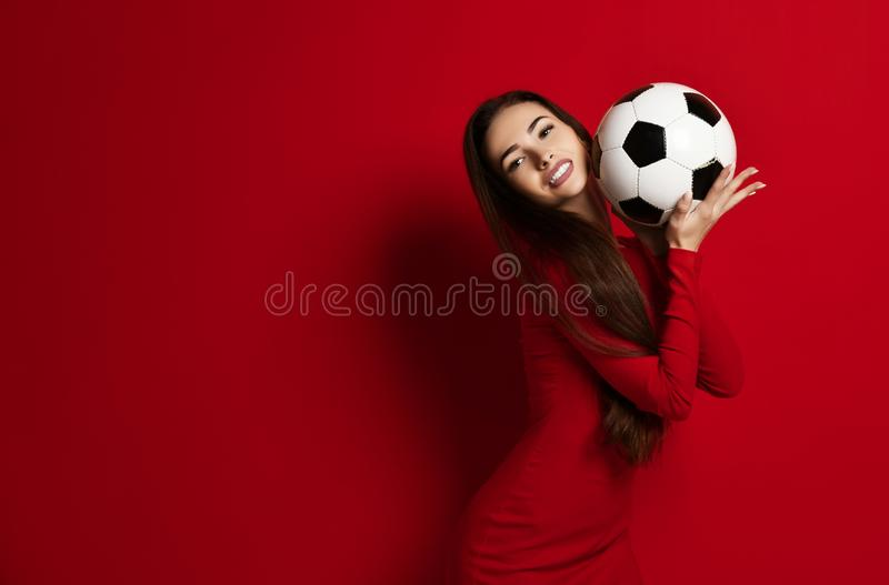 La jolie femme en rouge serré s'est penchée le ballon de football à sa joue comme elle l'embrasse sur le fond avec l'espace des t photo libre de droits