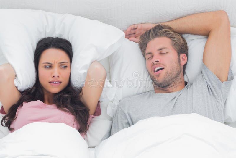 La jolie femme a ennuyé par le ronflement de son mari photos libres de droits