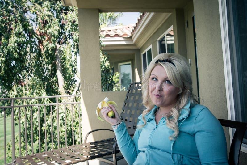 La jolie femme féminine blonde mange une banane sur un patio extérieur photographie stock