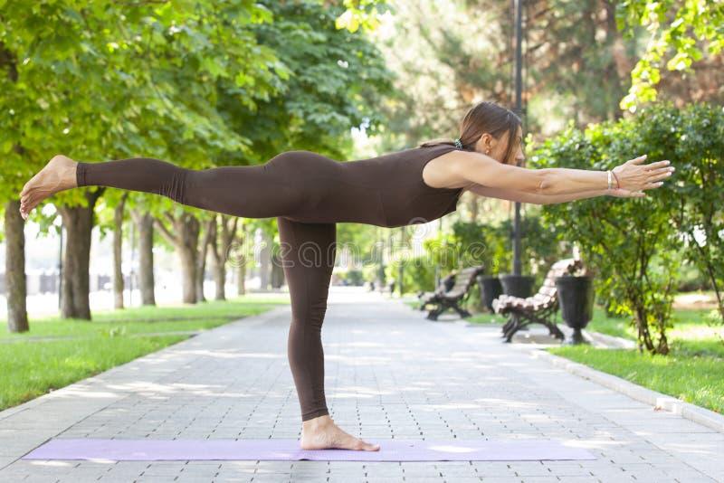 La jolie femme faisant le yoga s'exerce en parc photos stock