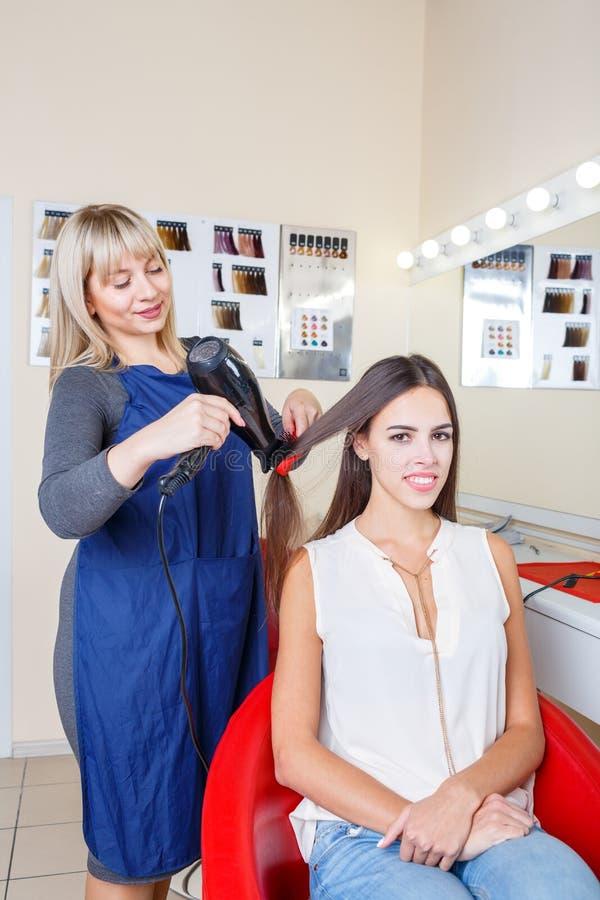 La jolie femme positive dans un raseur-coiffeur lui obtenant des cheveux a teint sur un fond brouillé Concept de Hairstyling photos stock
