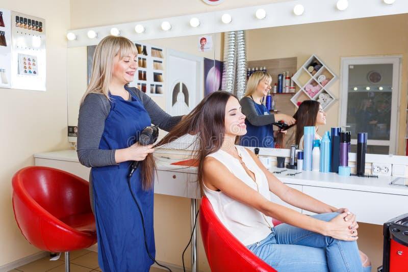 La jolie femme positive dans un raseur-coiffeur lui obtenant des cheveux a teint sur un fond brouillé Concept de Hairstyling images libres de droits
