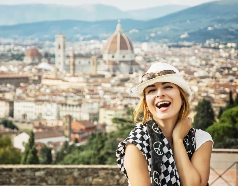 La jolie femme rit heureusement avec la ville de Florence derrière elle images stock