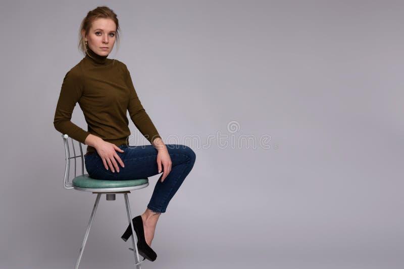 La jolie femme s'assied sur la chaise photos stock