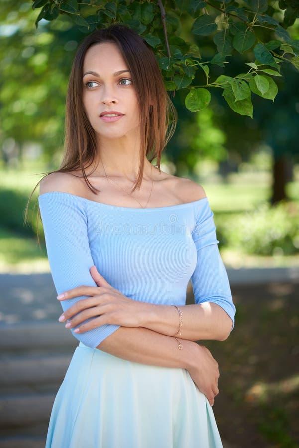 La jolie femme se tient en parc de ville Dehors portrait images libres de droits