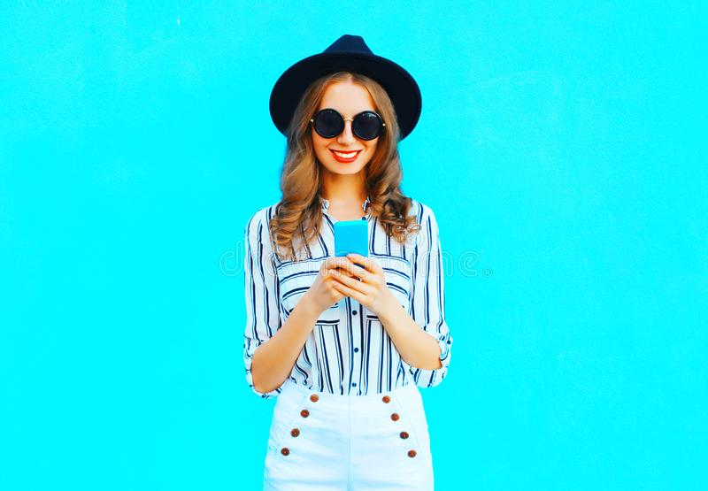 La jolie femme utilise un smartphone utilisant un chapeau noir et un sac à main images libres de droits
