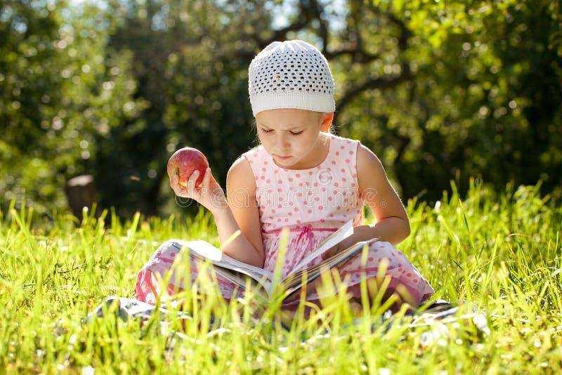 La jolie fille affiche un livre d'enfants photographie stock