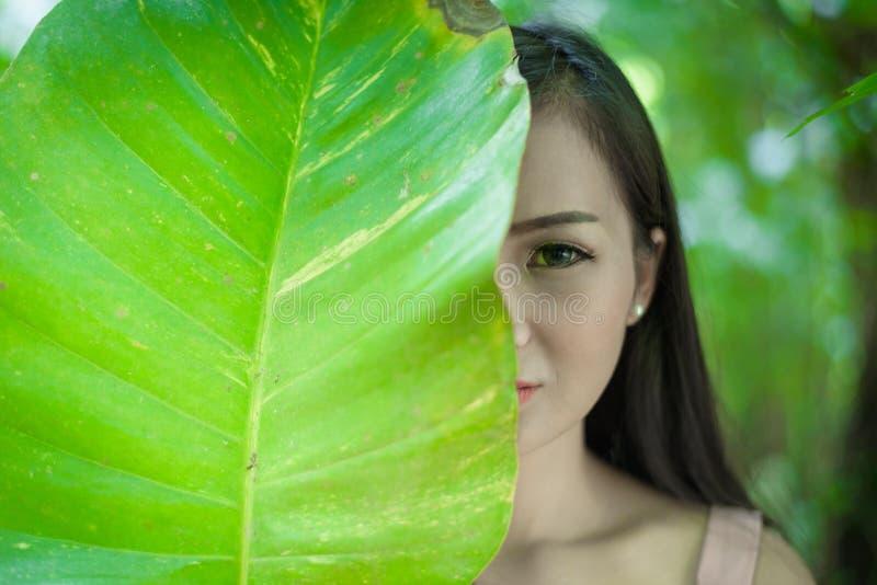 La jolie fille asiatique a l'oeil droit se fermant avec la fin vers le haut du concept à photographie stock libre de droits