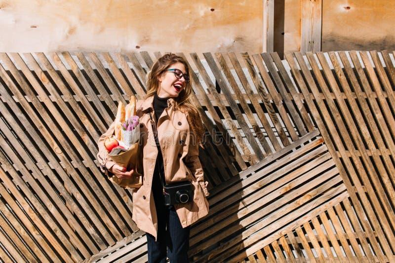 La jolie fille blanche habillée dans le manteau brun a acheté les pâtisseries fraîches à un petit prix Jeune femme élégante en ve images libres de droits