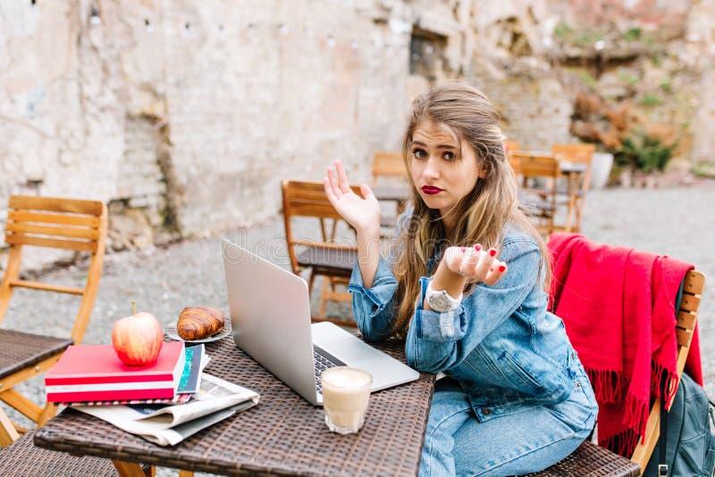 La jolie fille blonde inquiétée et étonnée, ne peut pas se relier à Wi-Fi public au café extérieur Mauvais Internet image stock