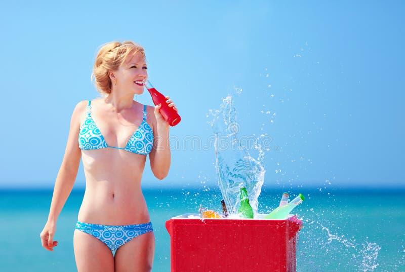 La jolie fille boit les boissons fraîches sur la plage image libre de droits
