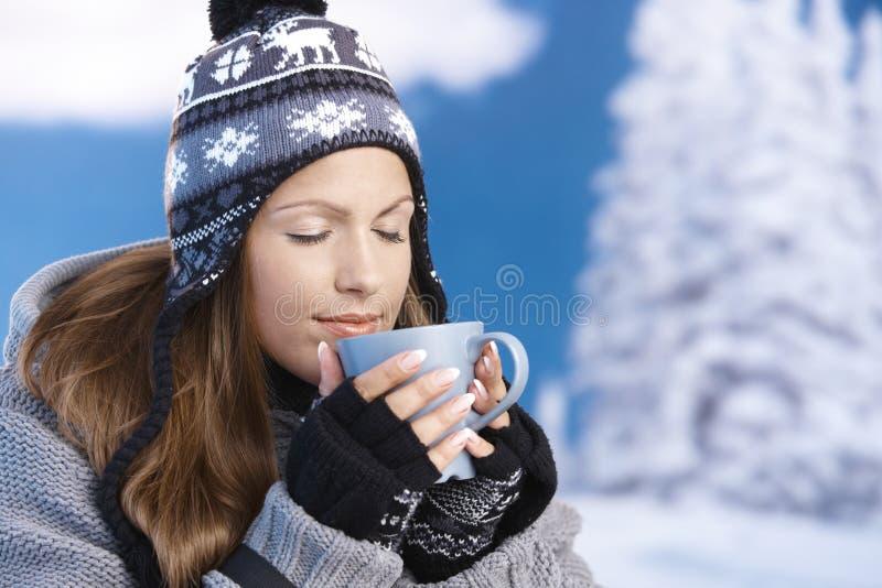La jolie fille buvant du thé chaud en yeux de l'hiver s'est fermée image libre de droits
