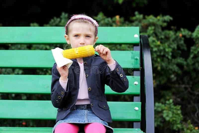 La jolie fille d'enfant mange d'un maïs bouilli à l'extérieur image libre de droits