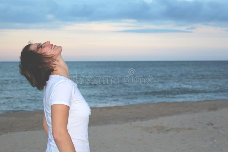 La jolie fille dans le T-shirt blanc sur la plage et recherche photo libre de droits