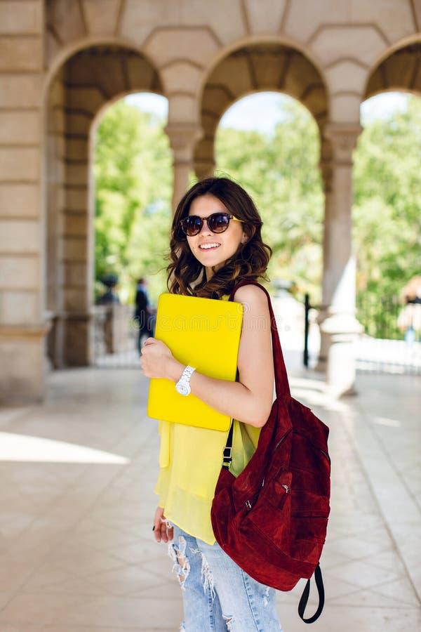 La jolie fille de brune dans des lunettes de soleil pose le sac vinicole de wirh sur le fond d'arcade Elle utilise la chemise jau photos stock