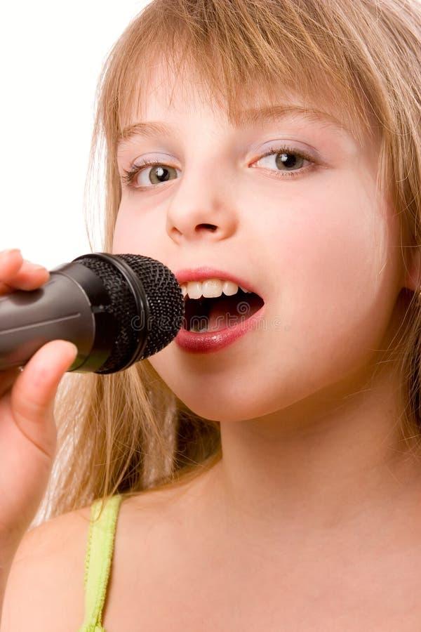 La jolie fille de litle chantant dans le microphone a isolé o images libres de droits