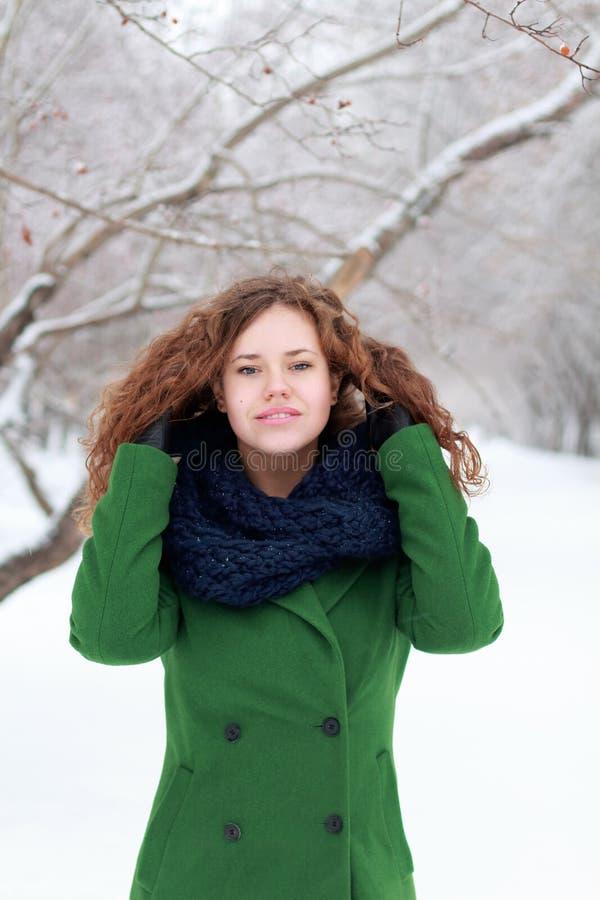 La jolie fille de sourire en vert touche ses cheveux à l'hiver image libre de droits