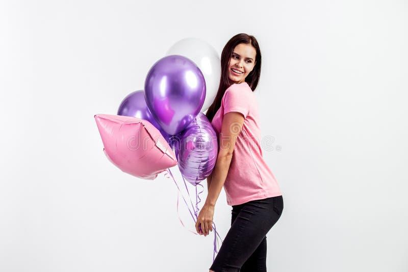 La jolie fille de sourire habillée dans le T-shirt et des jeans roses tient des ballons dans des ses mains sur le fond blanc dans photo stock