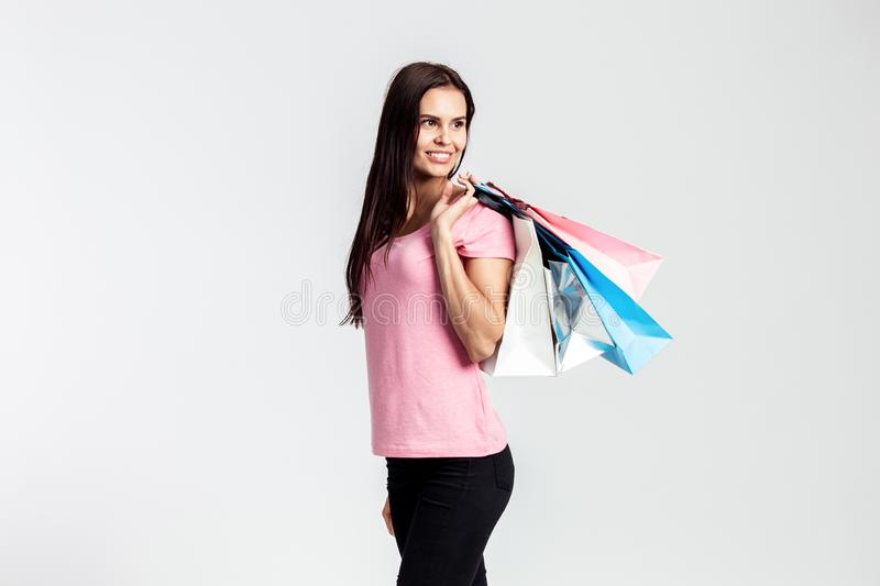 La jolie fille de sourire habillée dans le T-shirt et des jeans roses tient des sacs à provisions sur le fond blanc dans le studi photographie stock libre de droits