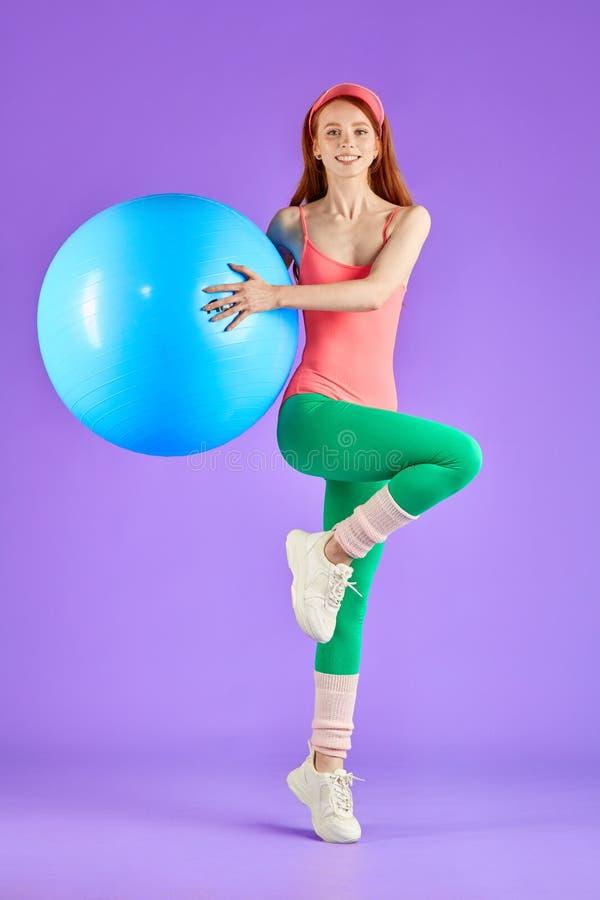 La jolie fille gaie sportive saute avec la boule convenable pendant l'aérobic photographie stock libre de droits