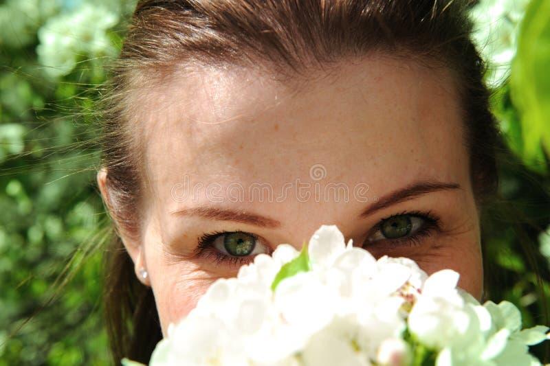 La jolie fille inhale l'arome de la fleur photos stock
