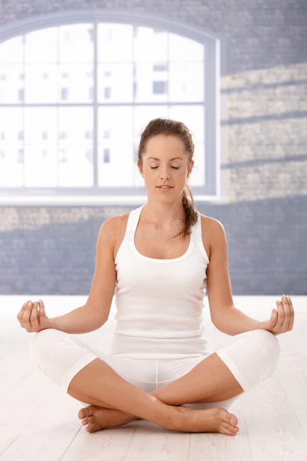 La jolie fille méditant dans des yeux de studio de yoga s'est fermée images stock