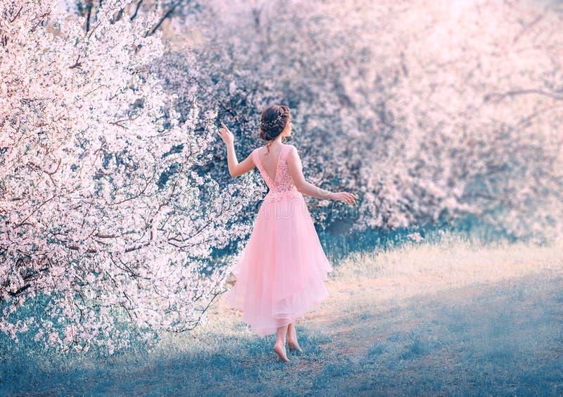 La jolie fille mince avec les cheveux fonc?s tress?s marche dans le jardin nu-pieds, princesse de for?t va exposer au soleil, dam photos libres de droits