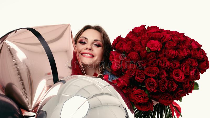 La jolie fille positive avec composent tenir le bouquet des roses rouges et des ballons à air photo stock