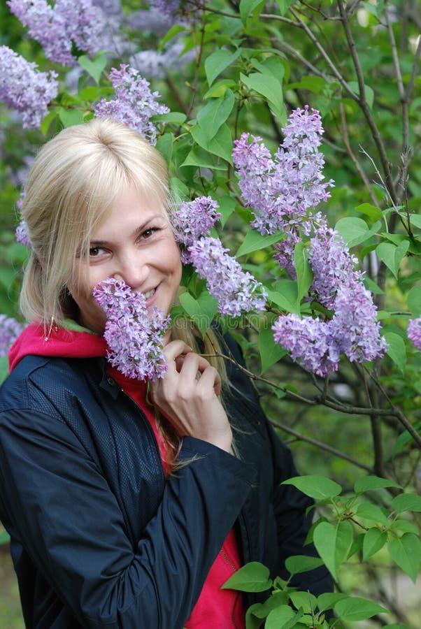 La jolie fille près d'un buisson d'un lilas photographie stock libre de droits