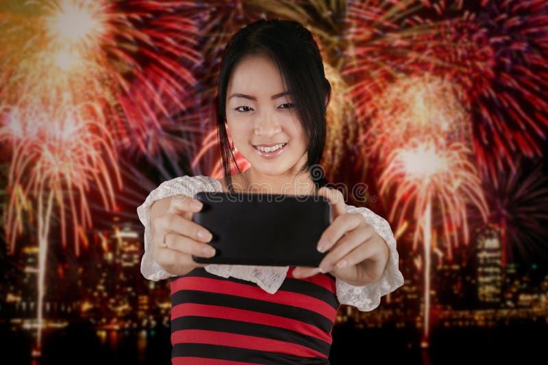 La jolie fille prenant le selfie aux feux d'artifice font la fête photos stock